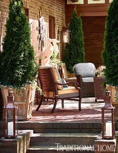 Library Terrace by Eric Ross for Summer Classics | With the home's beautiful brick exterior as a backdrop, the library terrace designed by Eric Ross acts as a natural extension, embracing the Tudor Revival style. Driftwood planters filled with arborvitae give a sense of enclosure while a variety of chair styles from Summer Classics forms a collected environment for lingering. A pair of dog statues stand guard atop the mahogany console table. Both the wall lantern and the lanterns lighting…