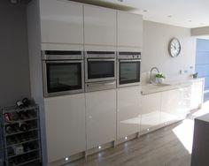 Tall Oven housings in gloss white incorporating eye level ovens