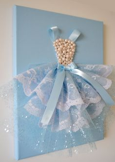 A beautiful sky blue princess dress on a 9x12 canvas would make a great accent in any girls room. Canvas is painted with acrylic paint and the princess dress is decorated with glittery tulle, ornate lace, silk ribbons and pearl beads