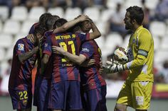 Ivan Rakitic (2ndR) celebrates scoring their opening goal with teammates as goalkeeper Juan Carlos Martin (R) of Cordoba CF reacts during the La Liga match between Cordoba CF and Barcelona FC at El Arcangel stadium on May 2, 2015 in Cordoba, Spain.