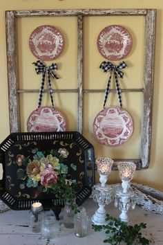 Kind of cute how she hung the red toile plates from homespun ribbons inside an old window frame.