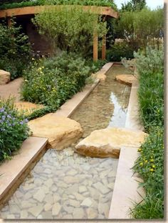The formal design of this water feature is softened by the planting. The stepping stones and path leading away add an air of mystery - an interesting combination