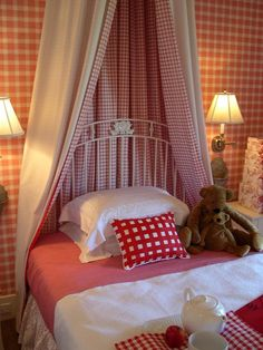Red and white walls, bedding and decor create a whimsical wonderland for children. A bed crown canopy and crisp, white furniture continue the Victorian theme in a playful, childlike way.