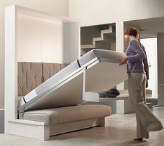 Neatest murphy bed I've seen! A shelf over the couch hinges into bed legs when pulled down!