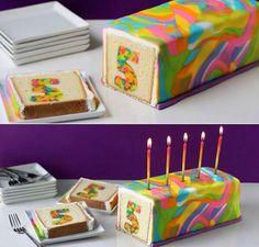 Gekleurde cake maken en in plakjes snijden. Gewoon beslag maken, laagje in de cakevorm en dan de gekleurde vorm in het gewone beslag zetten. Rest van het gewone beslag erbij en in de oven zetten.