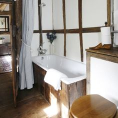 untreated timber planks have been fitted around the bath, continuing the barn-style rustic theme. A gingham shower curtain adds a charming period touch, as do traditional accessories such as a wooden shoe horn