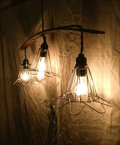 Machine age inspired pendant lights. Brass cage lights with vintage style bulbs, suspended from a repurposed truck leaf spring.