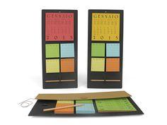 """""""Take a note"""" ημερολόγιο τοίχου 24 X 44εκ. Η βάση είναι κατασκευασμένη από ανακυκλωμένο δέρμα σε μαύρο/ γκρι χρώμα. Στο επάνω μέρος είναι κολλημένο το ημερολόγιο (οι μήνες και οι ημέρες σε 6 γλώσσες - όχι όμως στα ελληνικά) και στο υπόλοιπο τα 4 πακετάκια με χρωματιστά φύλλα σημειώσεων. Περιλαμβάνεται το μολύβι για το οποίο έχει προβλεφθεί και ειδική θήκη στη βάση. Έρχεται με χάρτινη συσκευασία στην περίπτωση που θα θέλατε να το δωρίσετε."""