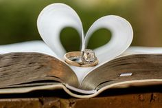 Wedding rings sitting on family bible with pages of bible making a heart shape.
