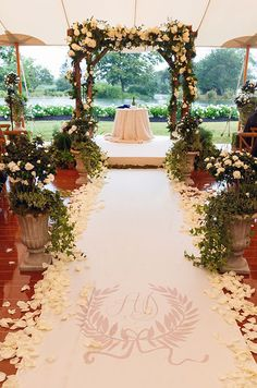 White rose petals line a monogrammed aisle that leads to a natural arbor