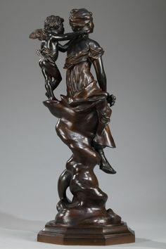Bronze sculpture with dark brown patination, featuring a dreamy young woman in a flowing dress holding a small bouquet of flowers. Behind her, a winged Cupid with his quiver whispers tender words in her ear. They are resting on a twisting tree trunk above an octagonal base. Signed on the base: Ch. Perron. $2,300.00