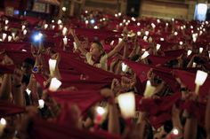 """Revellers hold up red scarves and candles during the closing ceremony of the San Fermin festival in Pamplona, northern Spain, early July 15, 2015. Thousands of people gathered in front of the city's town hall to sing the traditional farewell song """"Pobre de mi"""" (Poor me). The song is sung by revellers to show their sadness at the end of the festival. REUTERS/Susana Vera"""