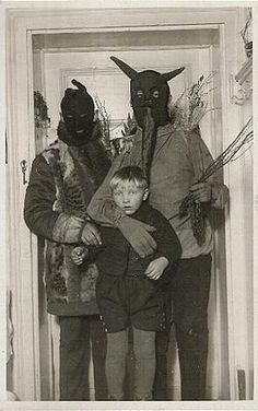 """I think I've figured out what the Hell is happening in this photograph: The guy wearing the horned mask is supposed to be """"Krampus"""" who was an old """"sidekick"""" of Santa Claus that punished naughty children with beatings using switches (in the guys left hand). Can anyone verify this?"""