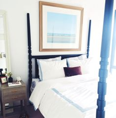 White bedroom with large art over canopy bed and white bedding with blue trim