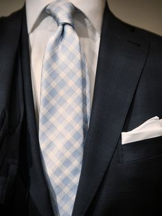 navy suit, white shirt, blue paterned tie, pocket square.
