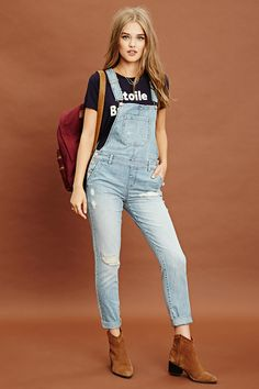 A pair of woven denim overalls with a snap-button front, adjustable straps, button sides, a square neckline, two back pockets, two front slit pockets, and a faux fly.