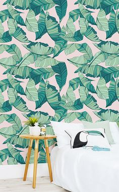 Obsessing over pink and green? Get the look with this tropical wallpaper design! Funky illustrated leaves are set against a pastel pink background. This weird and wonderful colour combination is a striking fit for playful bedroom spaces.