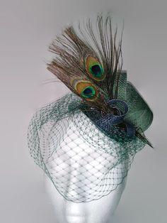 Tocado azul y verde de sinamay con velo plano verde y plumas de pavo real. Es un tocado perfecto para esta época con mayor frió que invita a llevar tonos