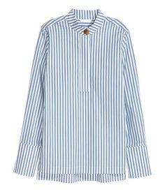 Azul/Rayas blancas. Camisa en tejido vaporoso de algodón con pequeño cuello elevado y botón grande de metal delante. Tapeta oculta, puños amplios con botón