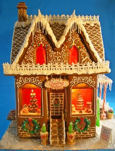 "Gingerbread house is approx. 15"" tall and 13"" wide. Baked goods, signs, and planters are made from gumpaste. Wrought iron is made from royal icing. Windows are made from isomalt but I couldnt get it clear so I left the front windows open! My dad made the template for this house and is the mastermind behind the elaborate construction! There are two night lights that light up the bay windows and one large light for the rest of the house. Took about a week and a day to make... whew...Thanks for…"