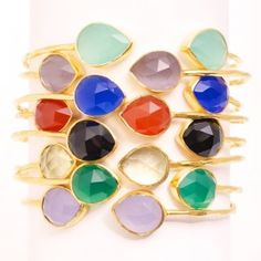 JC Cuff Group - Our bejeweled JC Cuff is the perfect way to add a little color to your wardrobe.  This gold plated adjustable cuff  has a textured finish and features two beautiful teardrop semi-precious gemstones. Worn alone or stacked,  the JC Cuff simply beautiful. As shown in the image from top to bottom, you may choose from seafoam, purple quartz, blue calcite, carnelian, black onyx, lemon quartz, green onyx, and lavender quartz.
