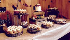 Rustic cake/ cupcake display with wooden platters and wooden crates. Garnished with fresh wild flowers. thebakersbox.net