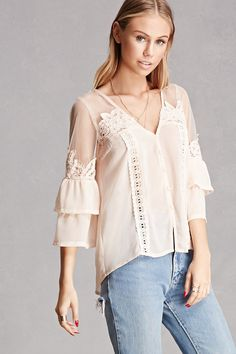 A woven top featuring a sheer mesh yoke, floral crochet panels throughout, tiered 3/4 sleeves, buttoned front, V-neckline, and a billowy silhouette. This is an independent brand and not a Forever 21 branded item.