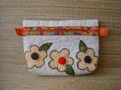Necessaire confeccionada em tecido de algodão cru, quiltada, forrada , com aplicação de flores coloridas. <br> Fechamento em zíper. <br>Medidas aproximadas: <br>Alt = 16 cm <br>Larg = 22 cm <br>Base = 5 cm X 18 cm