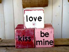 Conversation Blocks - How to make it: Cut your 4x4 post into perfect squares. Spray paint each block. For pink or cream blocks, spray a second coat, covering the red with pink or cream. Distress the edges with your sander. Wipe off each block with a lint-free rag to remove any excess dust. Apply desired vinyl lettering.