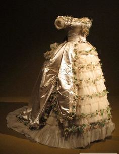 1869 wedding gown of Elisabeth of Wied, Queen Consort of Romania in The dress is made of silk satin, silk tulle with cotton and paper faux flowers. Held at FIDM.