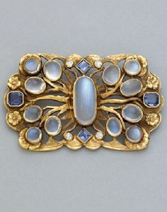 AN ARTS AND CRAFTS JEWELLED GOLD BROOCH, ca. 1920. Set with moonstone cabochons, calibré-cut sapphires and old mine-cut diamonds on flowering forged openwork branches. Unsigned. #ArtsCrafts #brooch