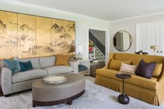 """The console table behind the center sofa holds a task reading light and serves as a sculptural element. """"It's also placed there to prevent the kids from hopping over the back of the sofa,"""" she says. To keep the space feeling cozy, the furniture needed to be smaller scaled—but that left a sizable 15-foot wall to fill. A 12-foot Chinese screen anchors the span and coordinates with the gold sofa."""