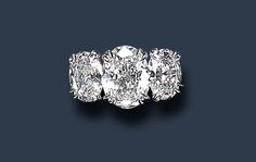 A THREE-STONE DIAMOND RING, BY HARRY WINSTON   Set with an oval-cut diamond, weighing approximately 2.78 carats, flanked on either side by oval-cut diamonds, weighing approximately 1.18 and 1.19 carats, mounted in platinum  Signed Winston for Harry Winston  With jeweler's mark for Harry Winston