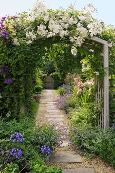 Fragrant blooms climb over a garden trellis and line the pathways of this charming country cottage garden.