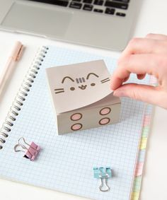 "This adorable Pusheen sticky note cube is perfect for fans of the comic and cat lovers alike! This sticky note cube is a Hey Chickadee Exclusive and not available anywhere else! Each sticky note sheet measures 3"" x 3"" and featured the chubby grey kitty's face. The sticky note cube measured approximately 1.5"" in height."