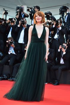 """Red Carpet Watch - Emma Stone's outfits seem to be synced partly with her chameleonic changes of coiffure. As it was for Rita Hayworth and Pippi Longstocking, red hair has become her signature, here worn with a forest-green, plunging-necklined tulle Valentino gown at the """"Birdman"""" premiere in Venice. (Photo: Gabriel Bouys/Agence France-Presse — Getty Images)"""