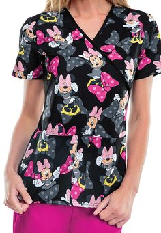 Bring some cheer to your office with the wonderful Peek-A-Bow scrub top featuring Minnie Mouse! This cute top is made with a slimming mock wrap design plus soft knit side panels. Two roomy patch pockets give you plenty of room to hold your accessories.