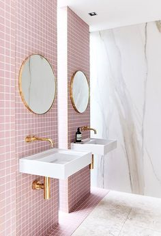 pink tiled bathroom. round gold mirror. small square tiles.