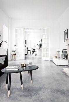 un grand salon avec sol en béton ciré gris et table en bois noire