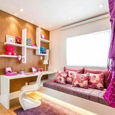Quarto de menina em tons de lilás, roxo e rosa, marcenaria branca e parede revestida em madeira.