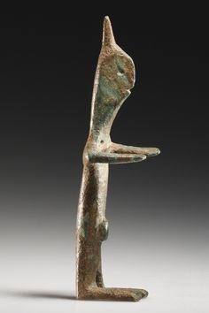 A Statuette of a Worshipper    H. 10 cm. Bronze  Iberian, 6th cent. B.C.    Schematic, almost geometric, flat figurine with outstretched arms, broad hands, large feet and pointed headdress. Important details such as the round, punched eyes, the grooved mouth and the genitals are rendered with economy. Reverse smooth. Intact.
