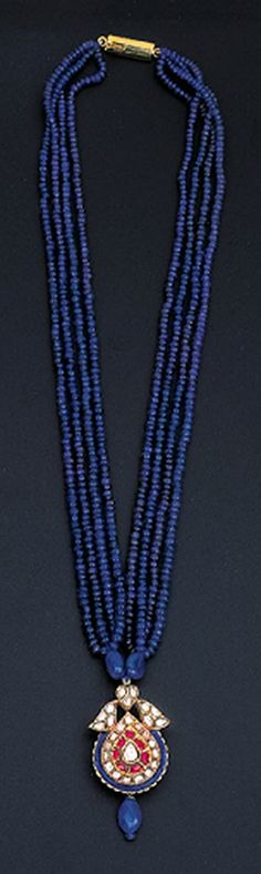 A DIAMOND AND SAPPHIRE PENDENT NECKLACE Centering upon a pear-shaped diamond-set pendant suspending a sapphire bead with foliate blue enamelled reverse to the four-row sapphire-bead necklace, pendant early 20th century, 28.0cm long