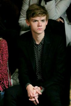 Thomas Brodie Sangster looking great in a black blazer and spotted shirt