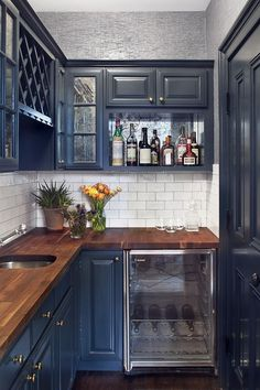 Beautiful blue kitchen with wet bar at the end.