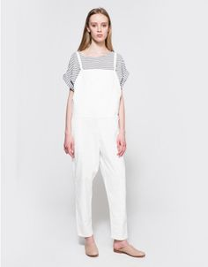 From Baserange, a modern organic cotton overall in White. Features adjustable straps with silver hardware, slanted front pockets, seem at waist, center seem from waist to leg, straight legs and a relaxed fit. • Overall in White • Adjustable straps •