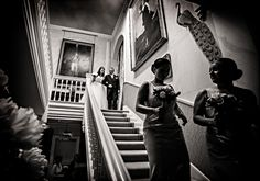Hodsock Priory Brides arrival down staircase by http://www.andrewfletcher.co.uk/reportage-wedding-photographer/