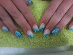 Blue gel with blue glitter sprinkled over, one full nail and rest slanted French with a white snowflake stamp on.