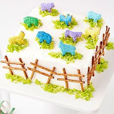 Bake a Barnyard - Cute idea - Stand frosted animal crackers on mounds of green-tinted coconut. Then build a fence with pretzel sticks and icing to create this cake.