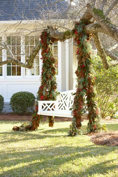 Christmas swag  with magnolia leaves, pinecones, seeded eucalyptus, Eastern red cedar, berries, and foliage hanging over outdoor swing.