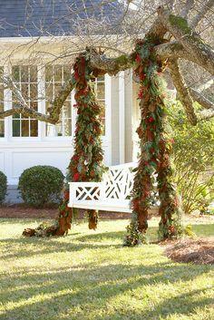 swing adorned with magnolia leaf garlands | via simply seleta